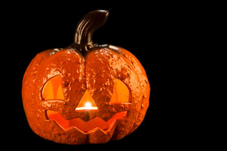Picture of a Halloween pumpkin with a candle inside on a black background. Stock Photo