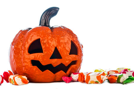 Picture of a Halloween pumpkin surrounded by candies on a white background. Stock Photo