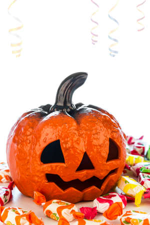 Picture of a ceramic pumpkin surrounded by candies in halloween party. Stock Photo