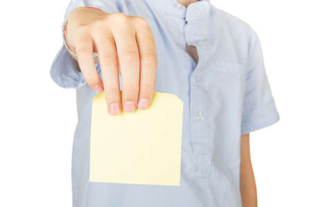 Child on white background showing a note at the camera.