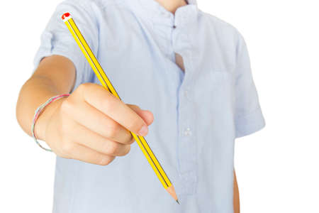 Child on white background showing a pencil at the camera. Stock Photo