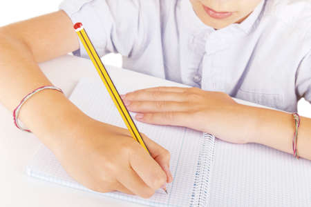 Boy writing with a pencil on a notebook at school. Stock Photo