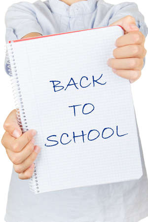 Child on a white background showing his notebook to back to school. Stock Photo