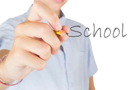 Student on white background writing the word school with a pencil.
