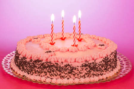Strawberry and chocolate cake with lighted birthday candles on a pink background. Stock Photo