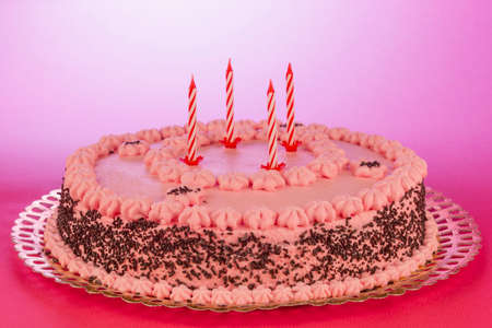 Strawberry and chocolate cake with unlit birthday candles on a pink background.