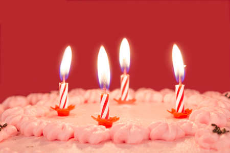 Burning birthday candles on a chocolate and strawberry cake on a pink background.