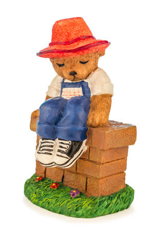 Figure of a little bear with clothes and hat sitting on a wall isolated on a white background. Stock Photo