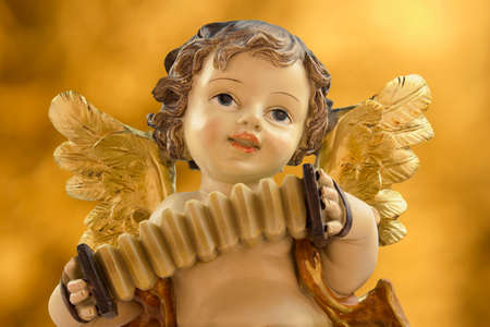 Figure of a Christmas angel playing an accordion on a golden background. Stock Photo