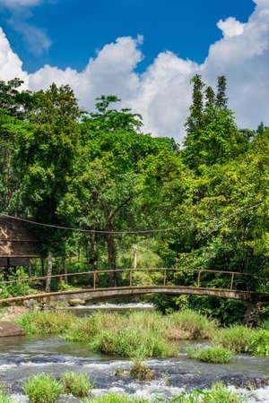 concrete foot bridge over a small river Stock Photo