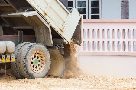 dumps: Dump truck dumps its load of rock and soil near the wall