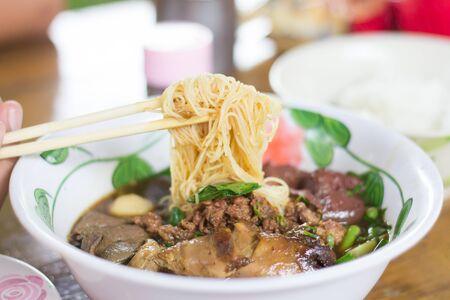 eating noodles: Eating noodles with chopsticks.