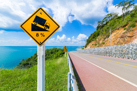 warning steep road sign slope and truck on hill Stock Photo