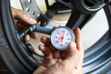 Hand holding pressure gauge for motorbike tyre pressure measurement Stock Photo
