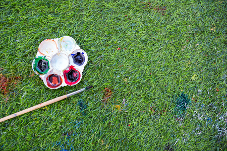 pallette: Palette and paintbrush on artificial grass
