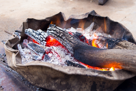relieve: Wood charcoal fire on the old basin , villager kindling to relieve cold weather.