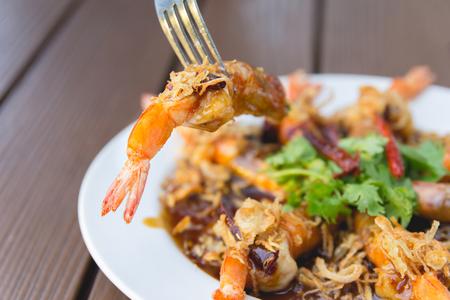 stabbing: Fork stabbing Fried Shrimp with Tamarind Sauce (Selective Focus)