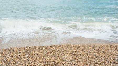 Tropical beach with shells and wave. Sea foam on beach. Paradise sea beach. Empty sea beach relax.