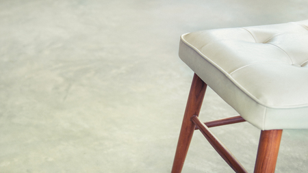 White leather chairs and wood chair legs with cement floor and space for text (vintage tone)
