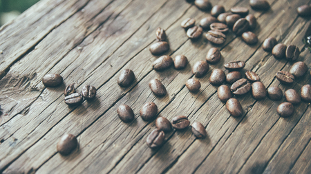 coffee beans on the wooden background (vintage film tone) Stock Photo