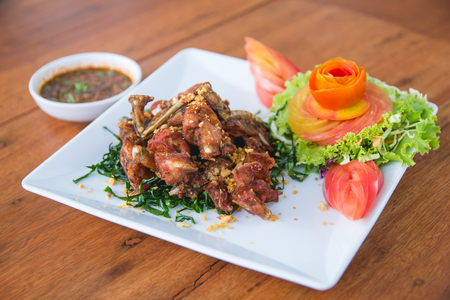 Fried Frog with Garlic on white plate amd wood table with tomato and vegetables