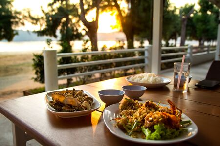 dining table with seafoods with golden light on sunset at seafoods restaurant nearby the beach