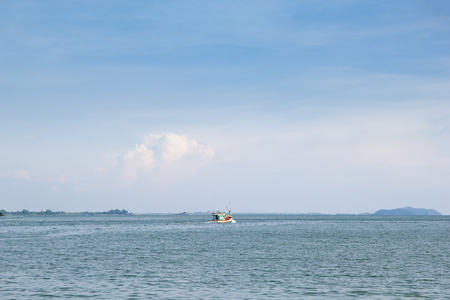 sky and sea with fisherman boat are driving out from the land , with space for text