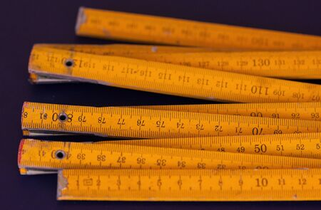 sectioned: Sectioned wooden old yellow rulers on blue background