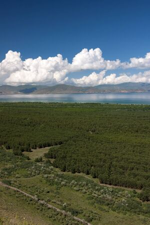 foamy: Green forests and mountains surrounding blue Sevan lake with foamy clouds