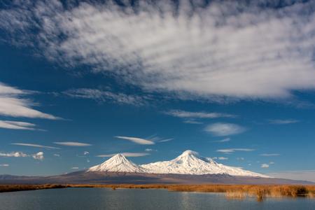 Blauw meer met riet en witte Ararat-berg met sneeuw en wolk op het