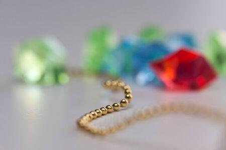 Gouden parelslinger op vage kleurrijke achtergrond
