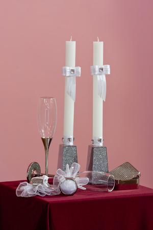 Reeks bruids glazen, ringen en witte kaarsen met boog en gem op roze achtergrond