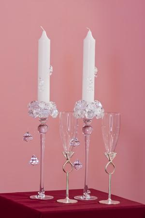 Paar witte bruids kaarsen met kristallen en twee glazen met ringen