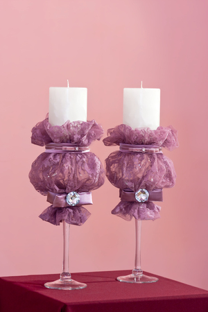 needle laces: Couple of white bridal candles with purple guipure and gems on pink background Stock Photo