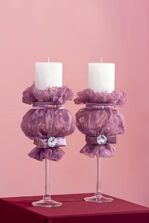 Paar witte bruids kaarsen met paarse guipure en edelstenen op roze achtergrond