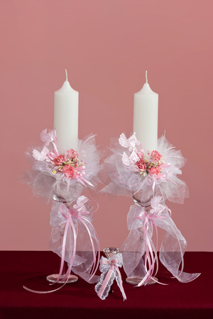 background patterns: Baby girl christening candles with artificial pink flowers and carriage ornaments