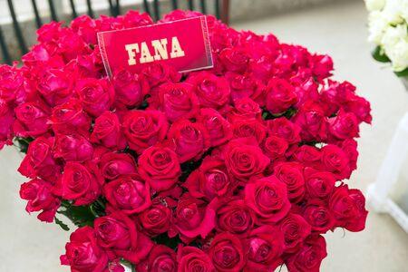 Bos van rode Fana-rozen met naametiket