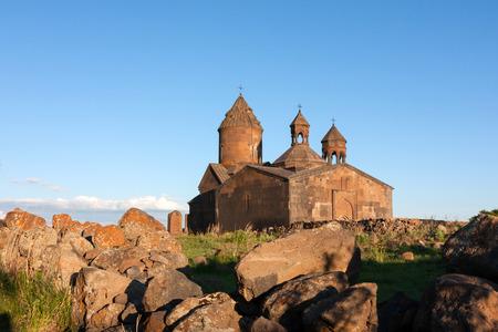 Zonlicht over armeense oude Saghmosavank-kerk met drie kruisen op de koepels