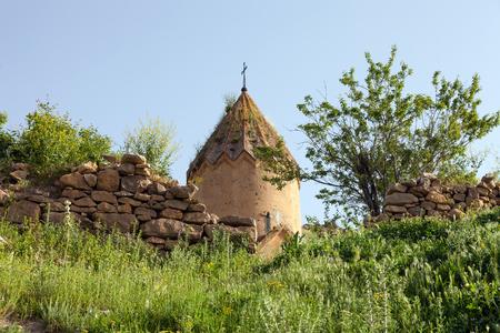 Geruïneerde stenen muren en de kerk Surb Karapet in wildgroen Stockfoto