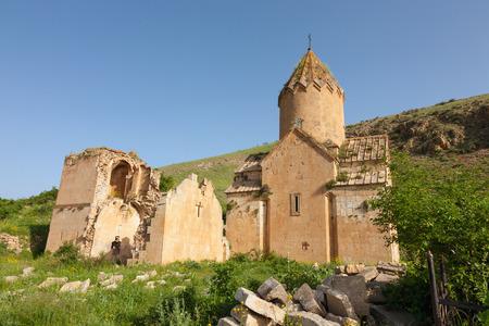 Mening van oude geruïneerde kerk Surb Karapet en stenen op een groene heuvel Stockfoto