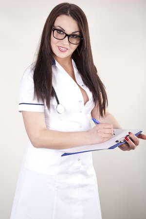 Beautiful young female doctor with patient list. photo