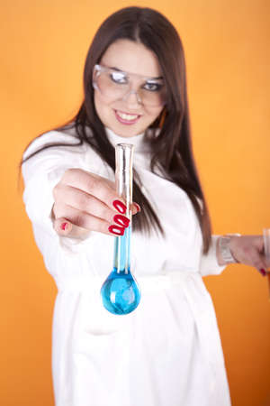 Young woman lab technician holding a test tube with blue liquid. photo