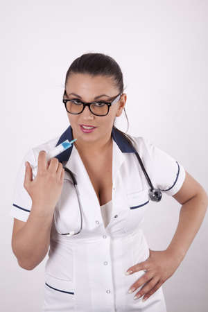 Beautiful young and sexy female doctor pointing sirynge to her lips. photo