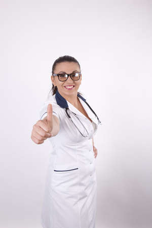 Beautiful young and sexy female doctor pointing thumb up. photo