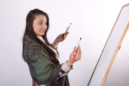 Young woman painting on white canvas. photo