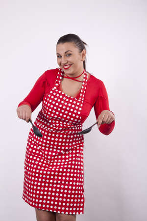 Young attractive housewife with kitchen tools. photo