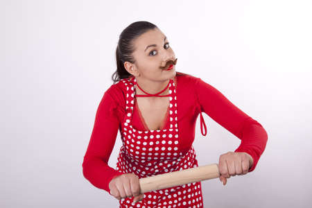 Young attractive housewife with rolling pin and moustaches. photo