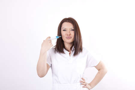 Young attractive female doctor pointing syringe to her cheeks and lips. Stock Photo - 13757133