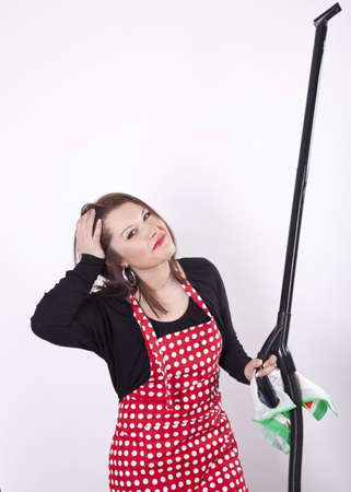 Young beautiful housewife holding vacuum cleaner. photo