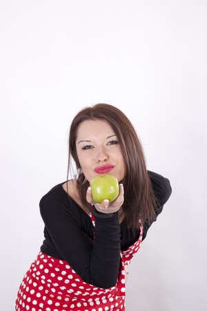 Young beautiful housewife holding green apple. photo